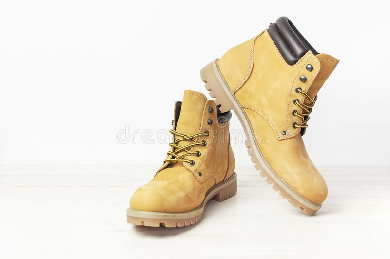 Yellow men`s work boots from natural nubuck leather on wooden white background. Trendy casual shoes, youth style. Concept of. Advertising autumn winter shoes royalty free stock photography