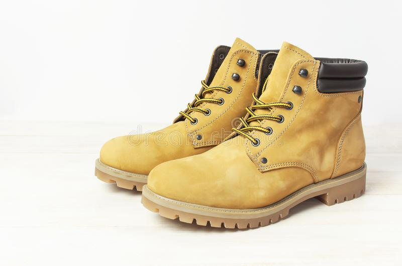 Yellow men`s work boots from natural nubuck leather on wooden white background. Trendy casual shoes, youth style. Concept of. Advertising autumn winter shoes royalty free stock image