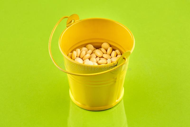 Yellow metal bucket with pills on green background.  stock images
