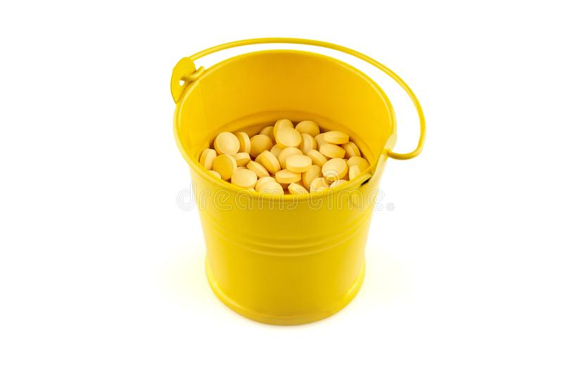 Yellow metal bucket with pills. Isolated in white background.  royalty free stock images