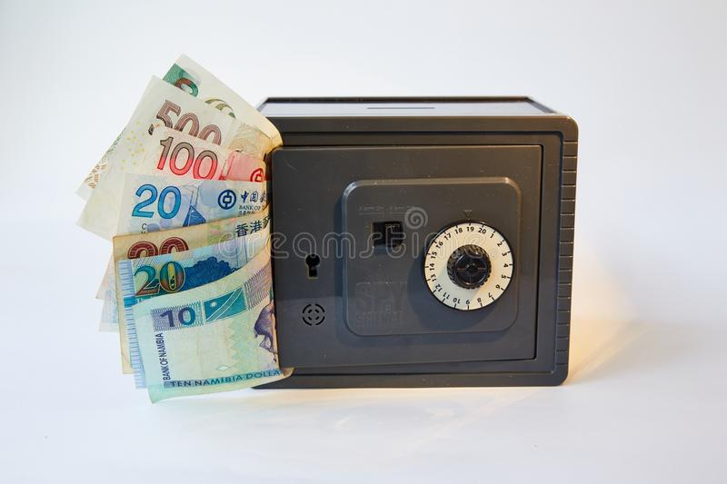 Yellow metal dollars and bills different currencies in gray safe, isolated stock images