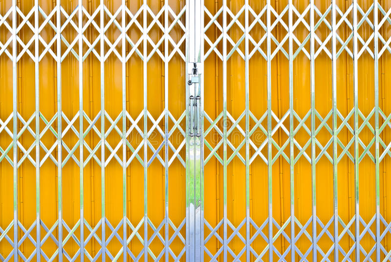 Yellow metal grille sliding door with pad lock royalty free stock photography