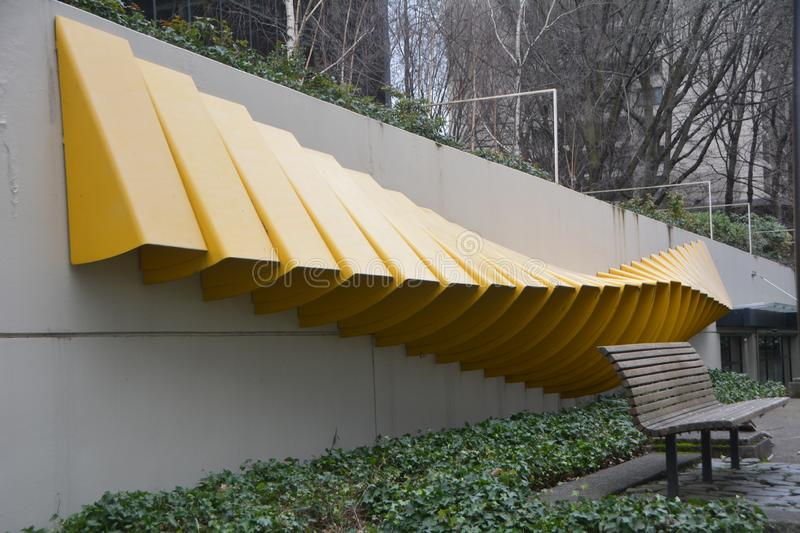 "Yellow retaining wall sculpture ""Awning"" in Portland, OR. This is a yellow metal sculpture on a retaining wall behind a bench in Portland, Oregon. The stock photos"
