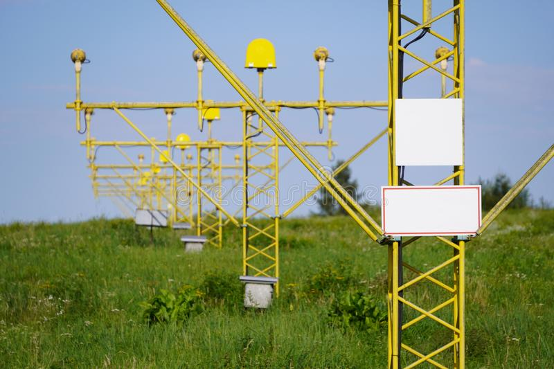 Yellow metal support systems of care during takeoff and landing - landing direction light near runway. air traffic safety stock images