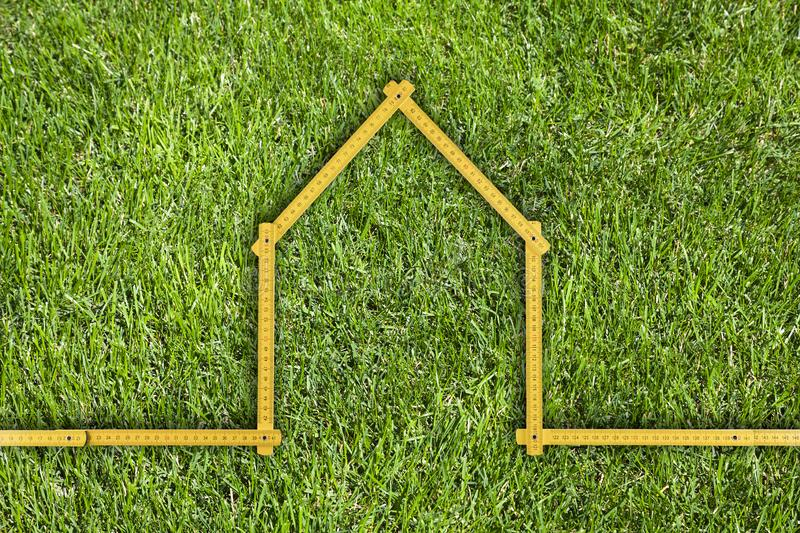 Yellow meter ruler folded as house on green grass. Yellow meter ruler folded as house over green grass royalty free stock images