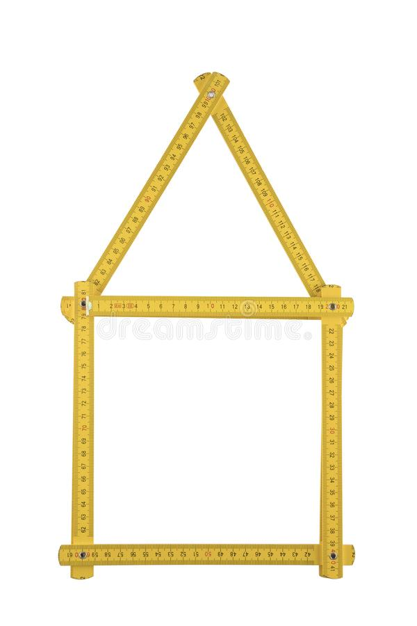 Yellow meter ruler folded as house. Isolated on white background royalty free stock photos