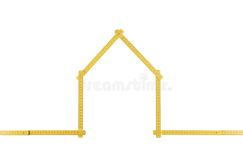Yellow meter ruler folded as house. On white background royalty free stock photo