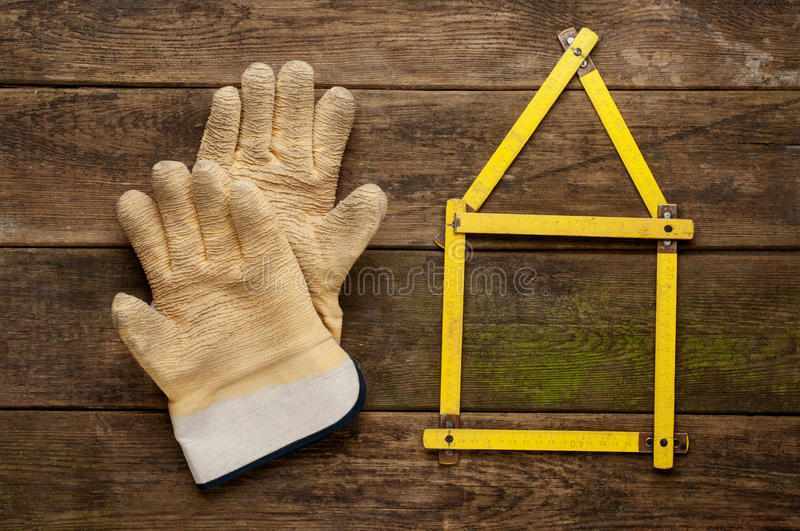 Yellow meter tool with pair of working gloves on vintage wooden background. Yellow meter tool with pair of working gloves on vintage wooden background stock photography