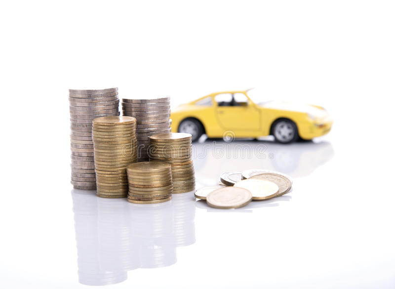 Yellow miniature car on a pile of stack coin. Isolated on white background royalty free stock photos