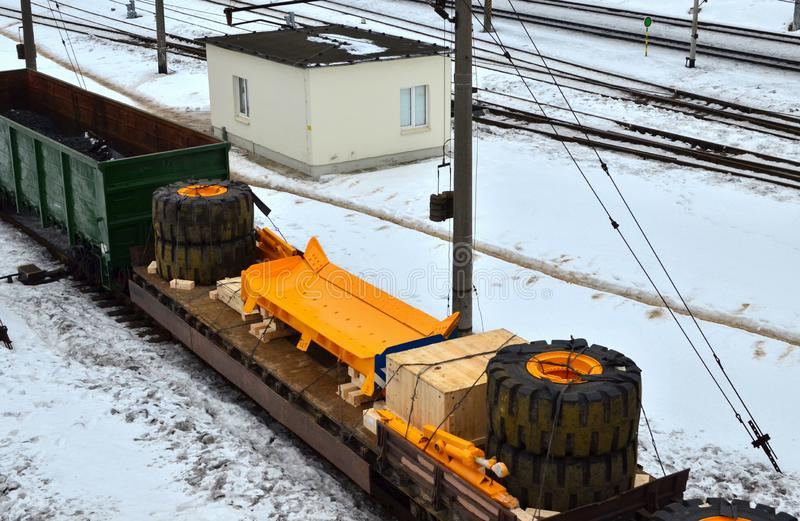 Yellow mining truck disassembled into parts, cab, body, electric motor, drive, wheels, loaded onto a cargo railway platform. stock photos