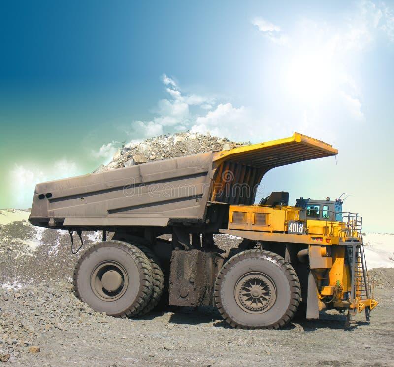 Yellow mining trucks. On sky royalty free stock photo