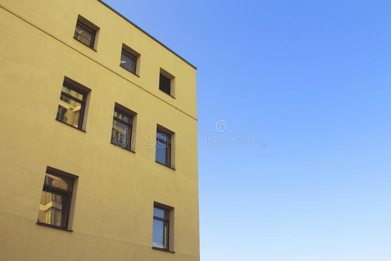 Yellow modern architecture building top corner on blue sky background royalty free stock images