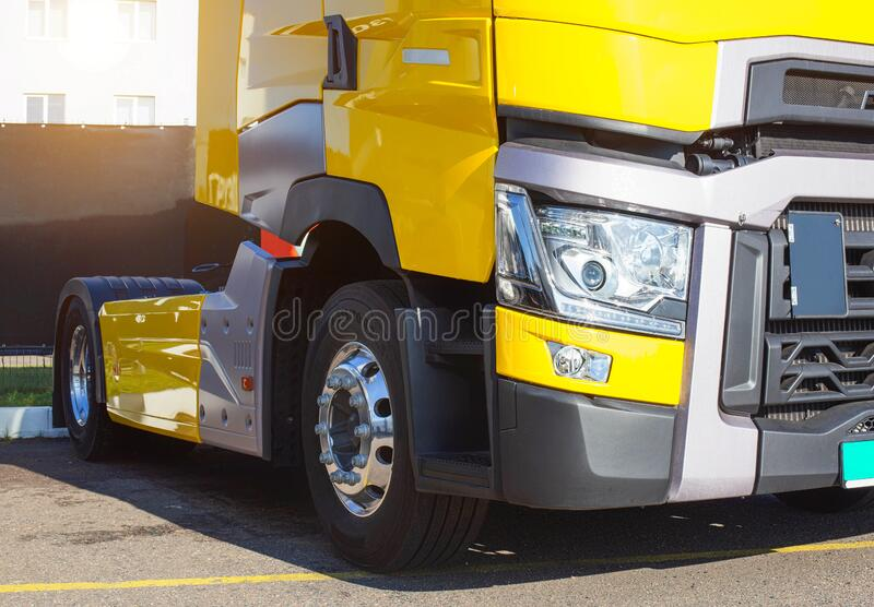 Yellow modern semi-trailer truck with modern LED headlights. Stylish and beautiful truck concept, logistic royalty free stock photos