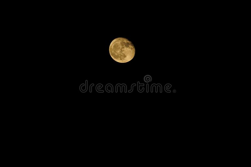 A yellow moon on a clear night stock photo