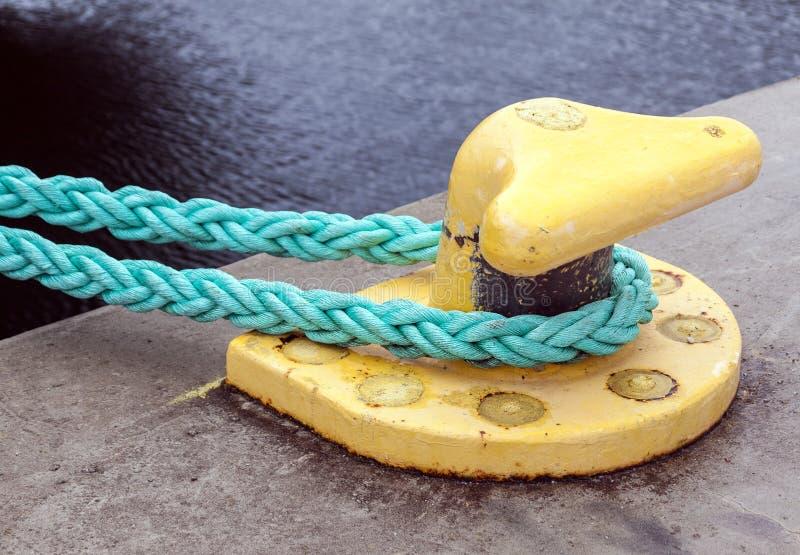 Yellow mooring bollard with green ropes royalty free stock images