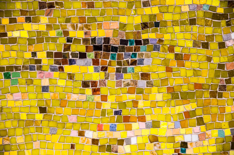 Yellow Mosaic Tile. Vintage wall mosaic with bright yellow rough cut tiles royalty free stock image