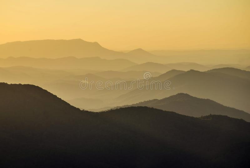 Yellow Mountaintop layers as the sun drops below the skyline. stock photography