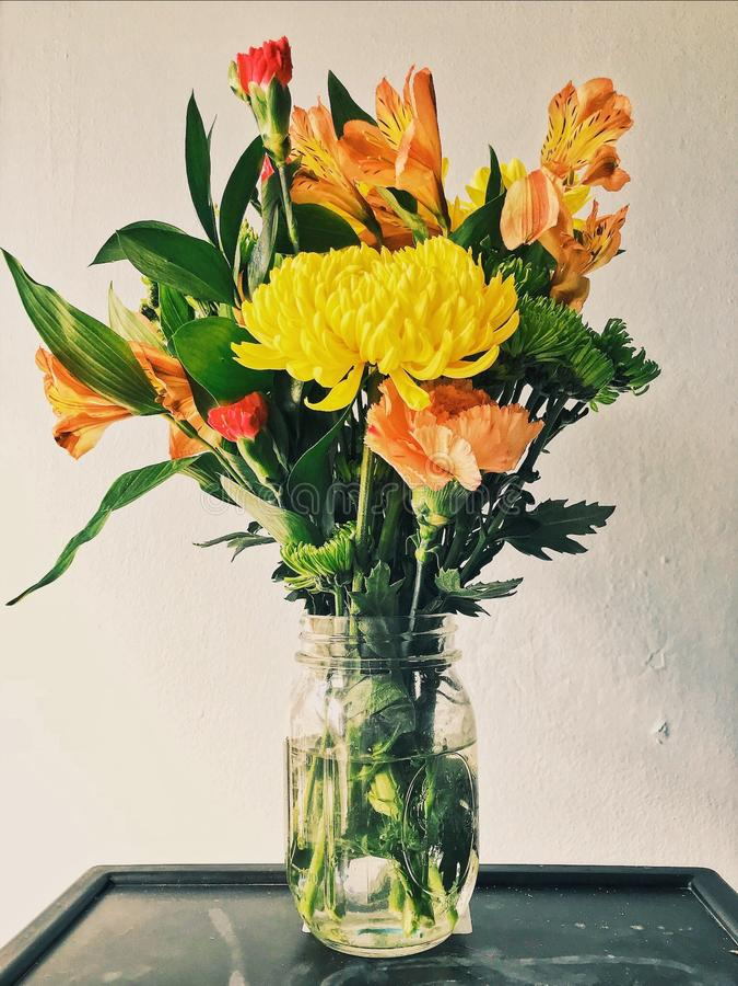 Yellow Mums, Orange Peruvian Lilies, and Carnation Flower Arrangement stock images