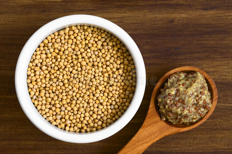 Yellow Mustard Seeds and Whole Grain Mustard. Yellow mustard seeds in bowl and whole grain mustard on wooden spoon, photographed overhead on wood with natural stock image