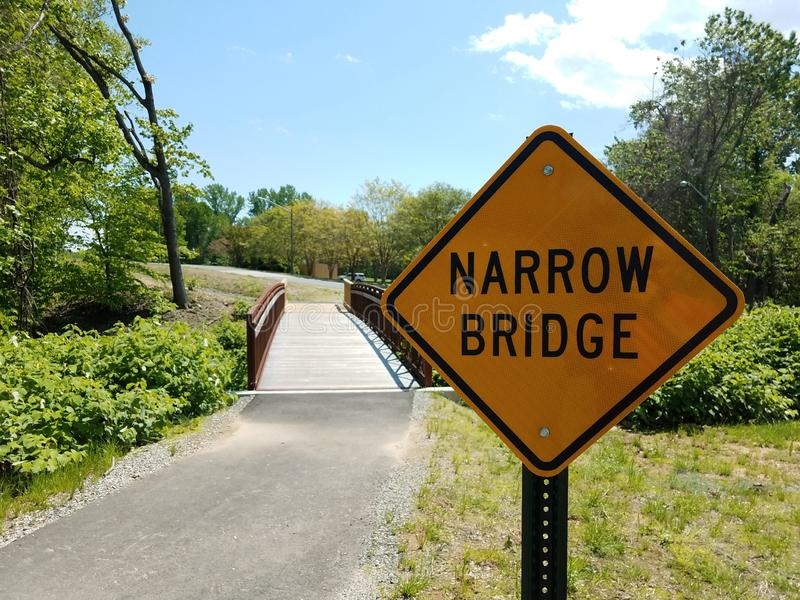 Yellow narrow bridge sign with bridge or path and trees. Yellow narrow bridge sign with bridge or path or trail and trees stock image