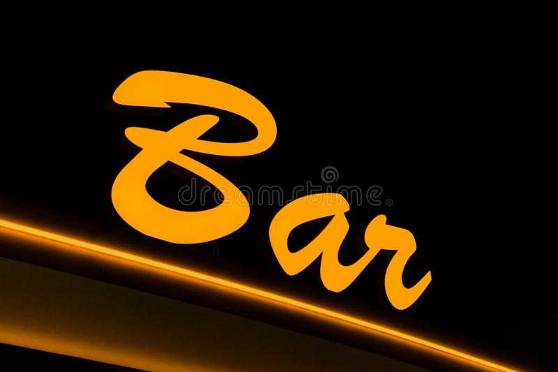 Yellow neon sign with the word BAR on a black background, close-up royalty free stock photo