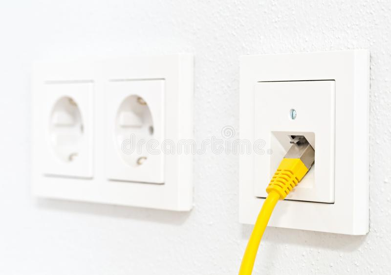 Yellow network cable in wall outlet for office or private home lan ethernet connection with power outlets flat view on white stock photos
