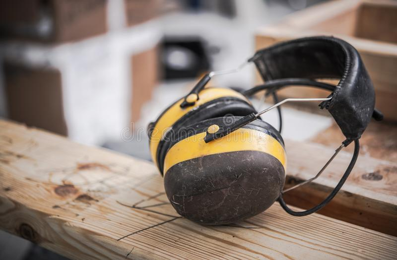 Noise Reduction Ear Muffs. Yellow Noise Reduction Safety Ear Muffs in the Construction Site. Safety Equipment royalty free stock photo