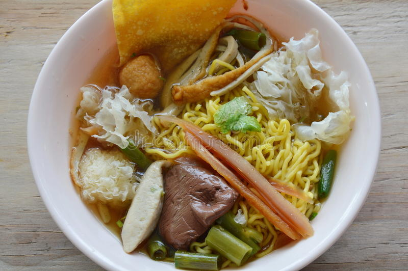 Yellow noodle with fish ball and crispy squid in soup royalty free stock photo