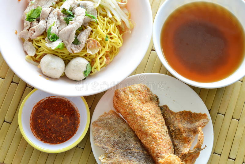 Yellow noodle topping pork ball and crispy fish skin with soup royalty free stock photos