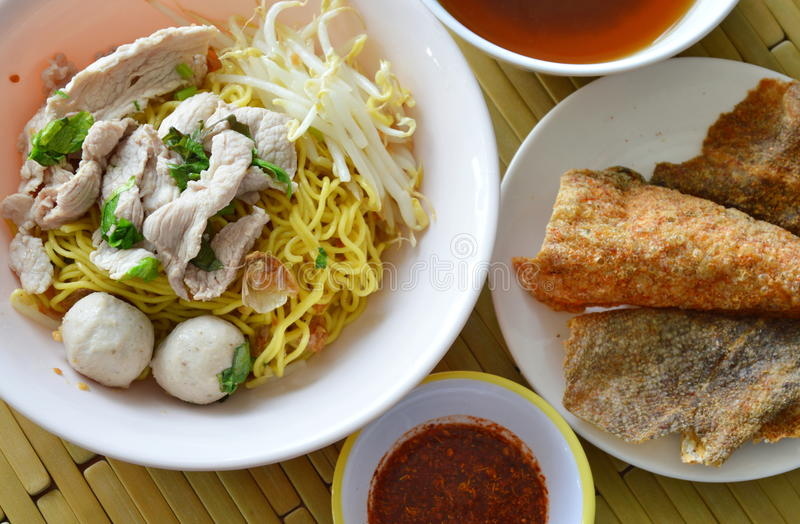 Yellow noodle topping pork ball and crispy fish skin with soup royalty free stock photography