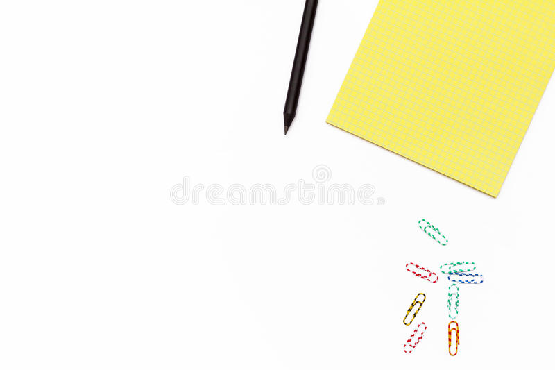 Yellow Notepad, black pencil, and colored paper clips on a white background. Minimal business concept. Flat law. royalty free stock photos