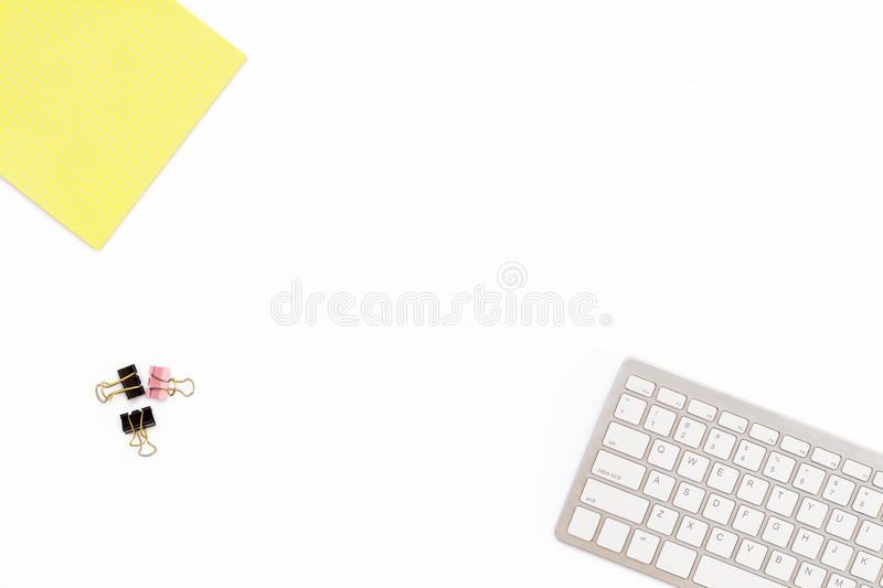 Yellow Notepad, computer keyboard and clips for paper on white background. Minimal business concept for desktop in the office. royalty free stock photography