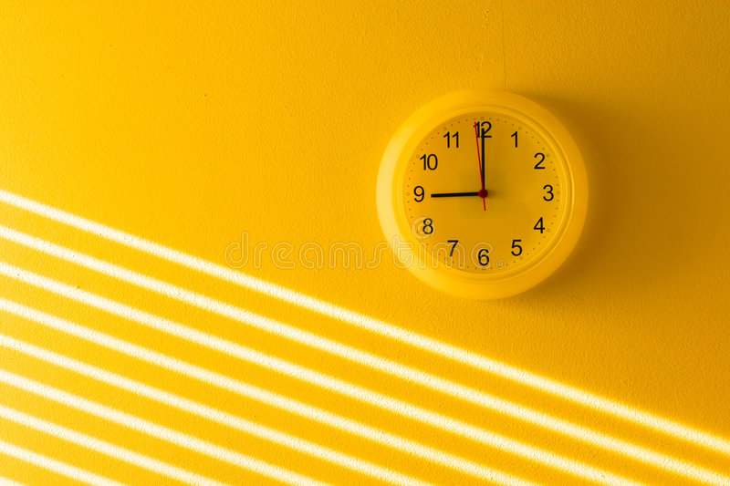 Yellow office clock. Yellow office wall clock background stock images