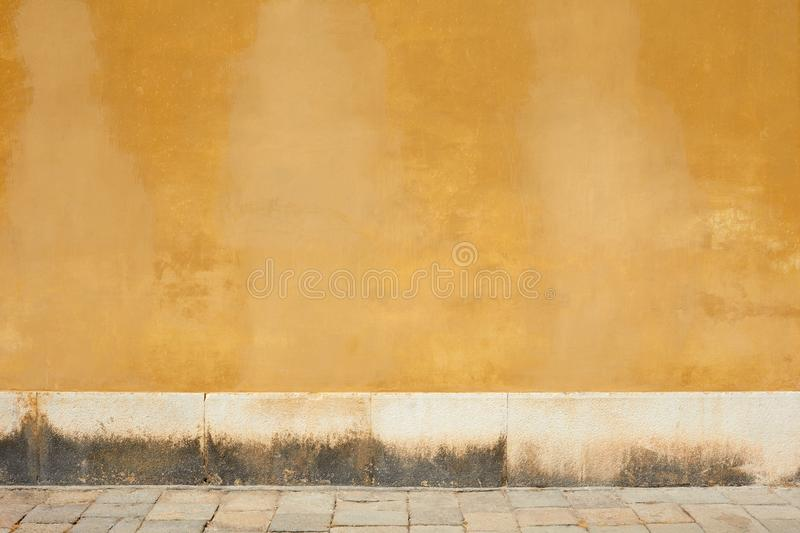 Yellow old faded wall and empty sidewalk. With stone tiles in Italy royalty free stock images