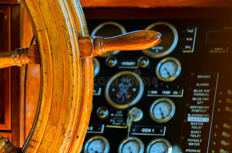 Yellow, old, lacquered, wooden steering wheel on a marine yacht, sensors and pointers with arrows in the background royalty free stock photos