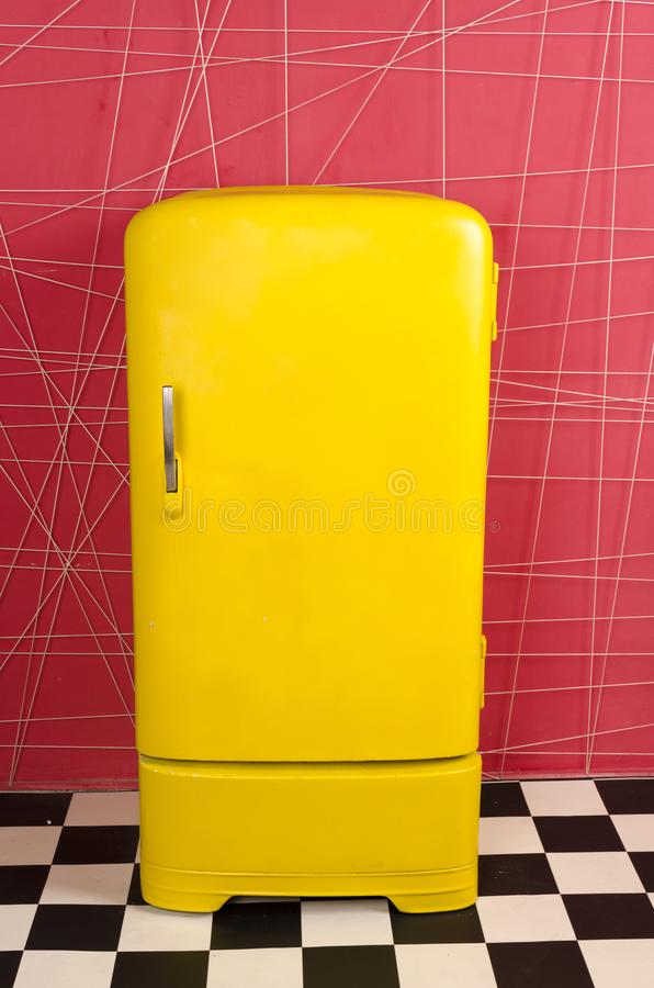 Yellow old vintage retro refrigerator on a pink background stock image