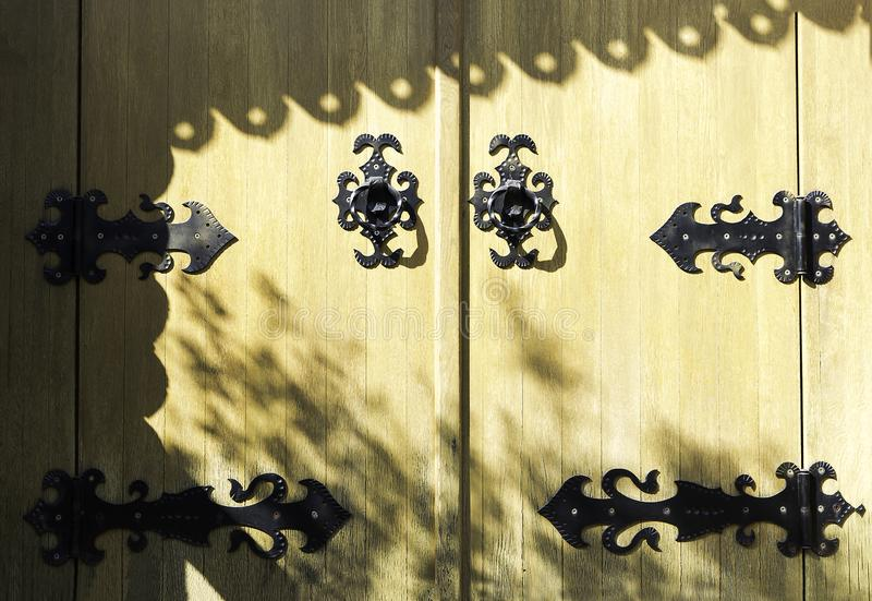 Yellow old wooden church door with metal design for decoration, Ancient church gate with black iron pattern, and shadows royalty free stock images
