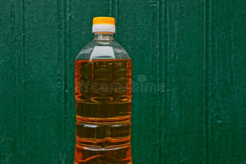 Sunflower oil in a plastic bottle on a green background. Yellow olive oil in a closed transparent plastic bottle on a green background stock photos