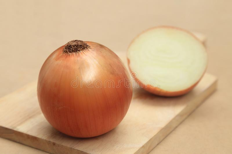 Yellow onion vegetable or gold onion bulb, whole and half on wooden chopping block royalty free stock photography