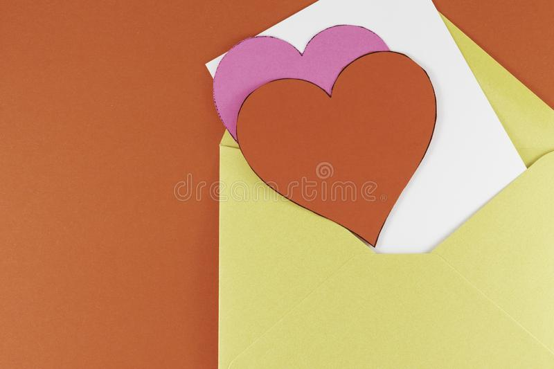 Yellow open envelope with white blank letter inside Big hearts of red and white colors on a red background. Letter or invitation Minimalist concept Copy Space royalty free stock photo