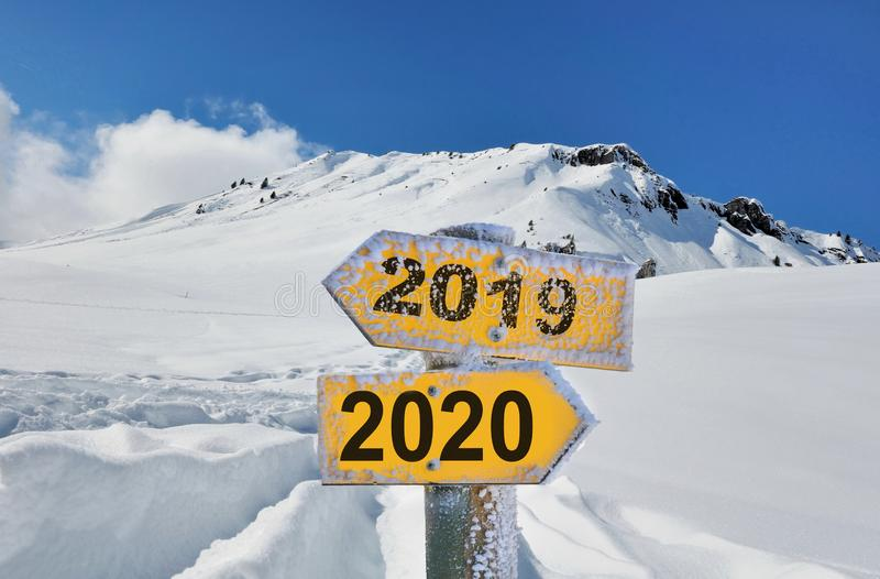 yellow panel 2019 and 2020 in front of snowy mountain landscape under blue sky royalty free stock photography