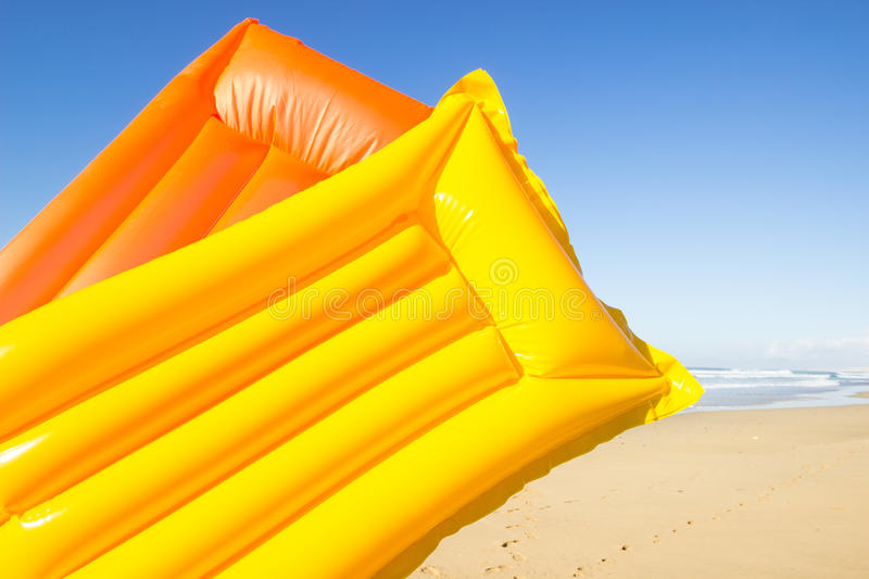 Yellow and orange air mattress. Travel background with a yellow and orange air mattress at an endless white beach with a blue sky and a turquoise sea, Playa de royalty free stock images