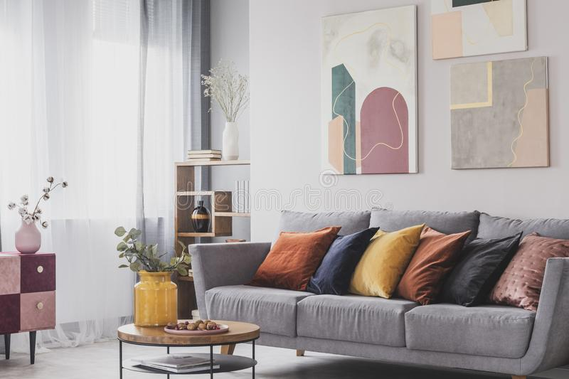 Yellow, orange, black and brown pillows on comfortable grey scandinavian sofa in bright living room interior with abstract royalty free stock photo