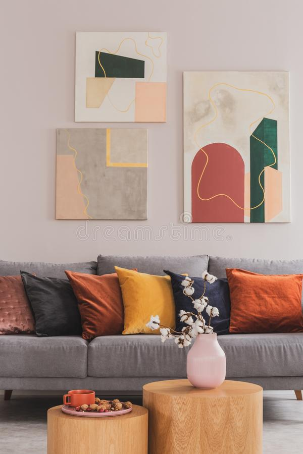 Yellow, orange, black and brown pillows on comfortable grey scandinavian sofa in bright living room interior with abstract royalty free stock photos