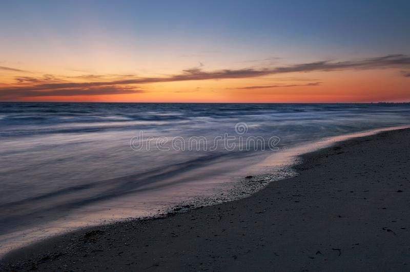 Yellow, orange and blue colors in twilight after sunset illuminate the sky and shiny, silky water along Barefoot Beach, Florida. At twilight royalty free stock image