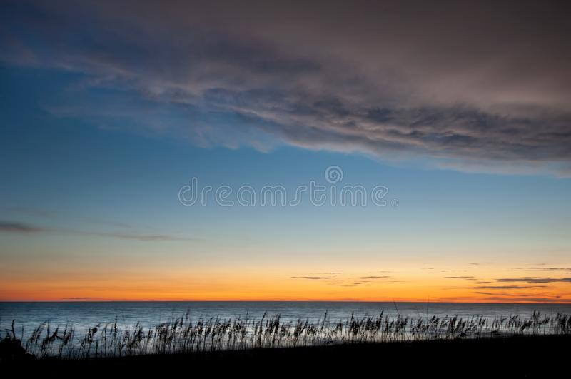 Sunset colors in twilight after sunset along the beach. Yellow, orange and blue colors in twilight after sunset illuminate a partially cloudy sky with shiny royalty free stock photo