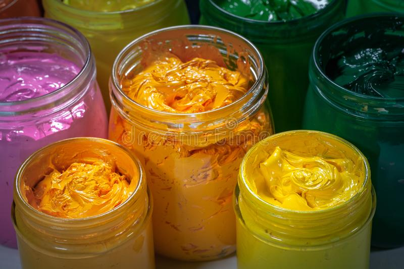 Yellow and orange colors of screen printing ink for print on tee shirts and fabric. Plastisol ink useful in tee shirt factory and textile for export royalty free stock image
