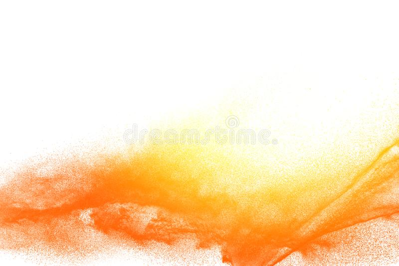 Yellow orange dust particles explosion on white background. Abstract powder dust splash royalty free stock photo