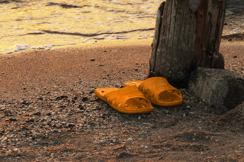 Yellow Orange flipflop on the sandy beach sea water background at sunset. Resorts of the Krasnodar Territory Sea of Azov. YellowOrange flipflop on the sandy royalty free stock images