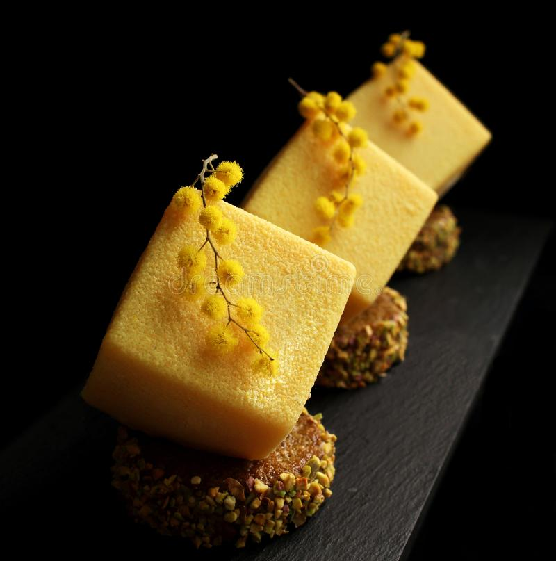 Orange mousse spring textured desserts on pistachio sponge cake slices with mimosa flowers royalty free stock photography